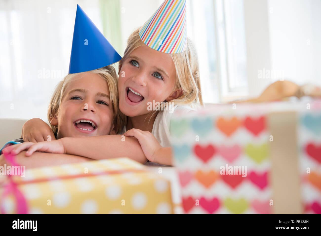 Fratello (4-5) e sorella (6-7) nell abbraccio alla festa di compleanno Foto Stock