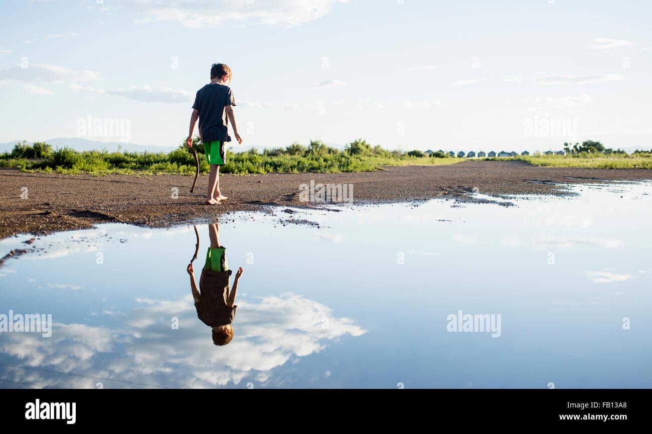 Ragazzo (6-7) passeggiate sulle rive del lago Immagini Stock