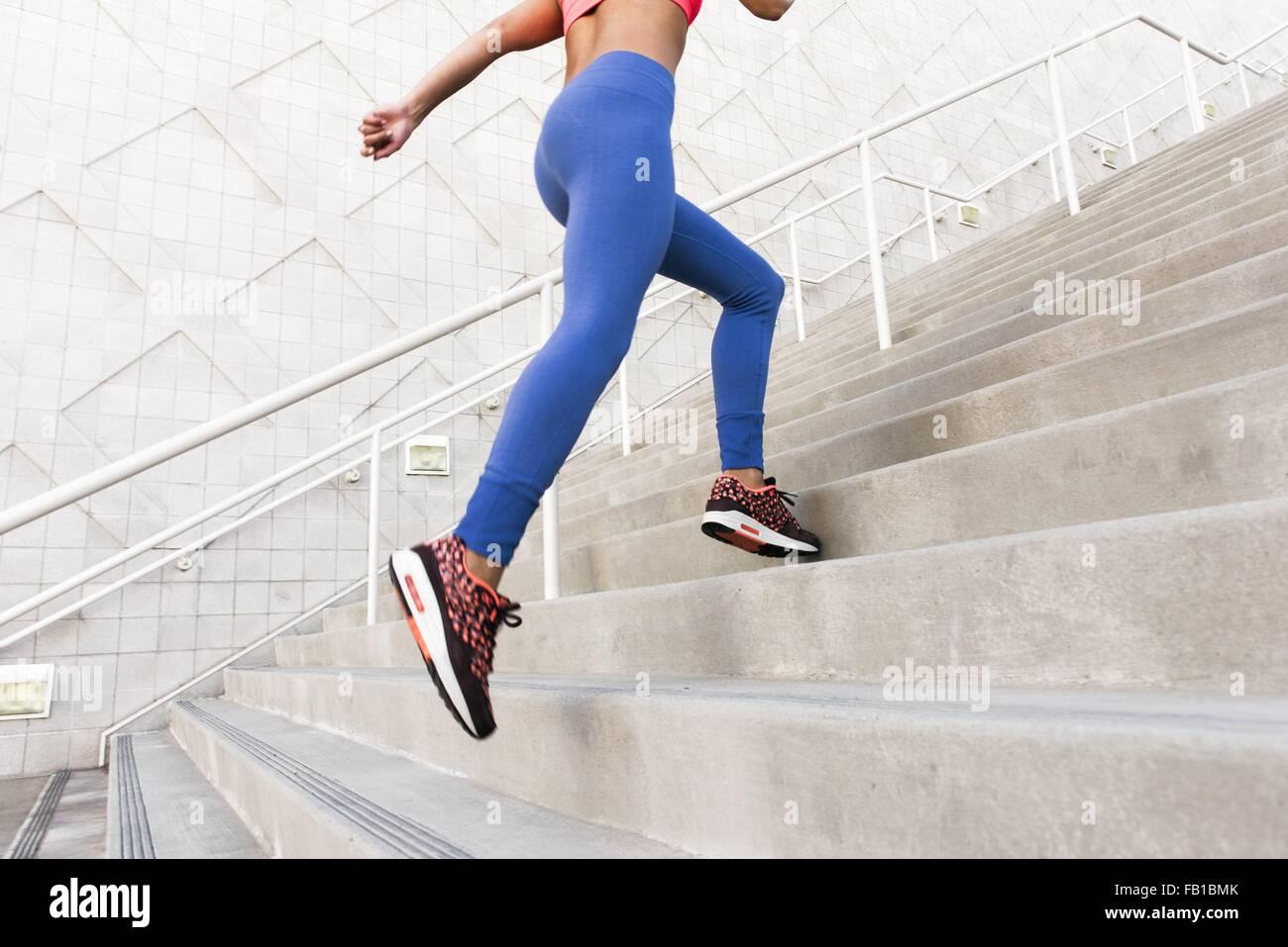 Basso angolo vista posteriore della giovane donna, che indossa abbigliamento sportivo in esecuzione su per le scale Immagini Stock