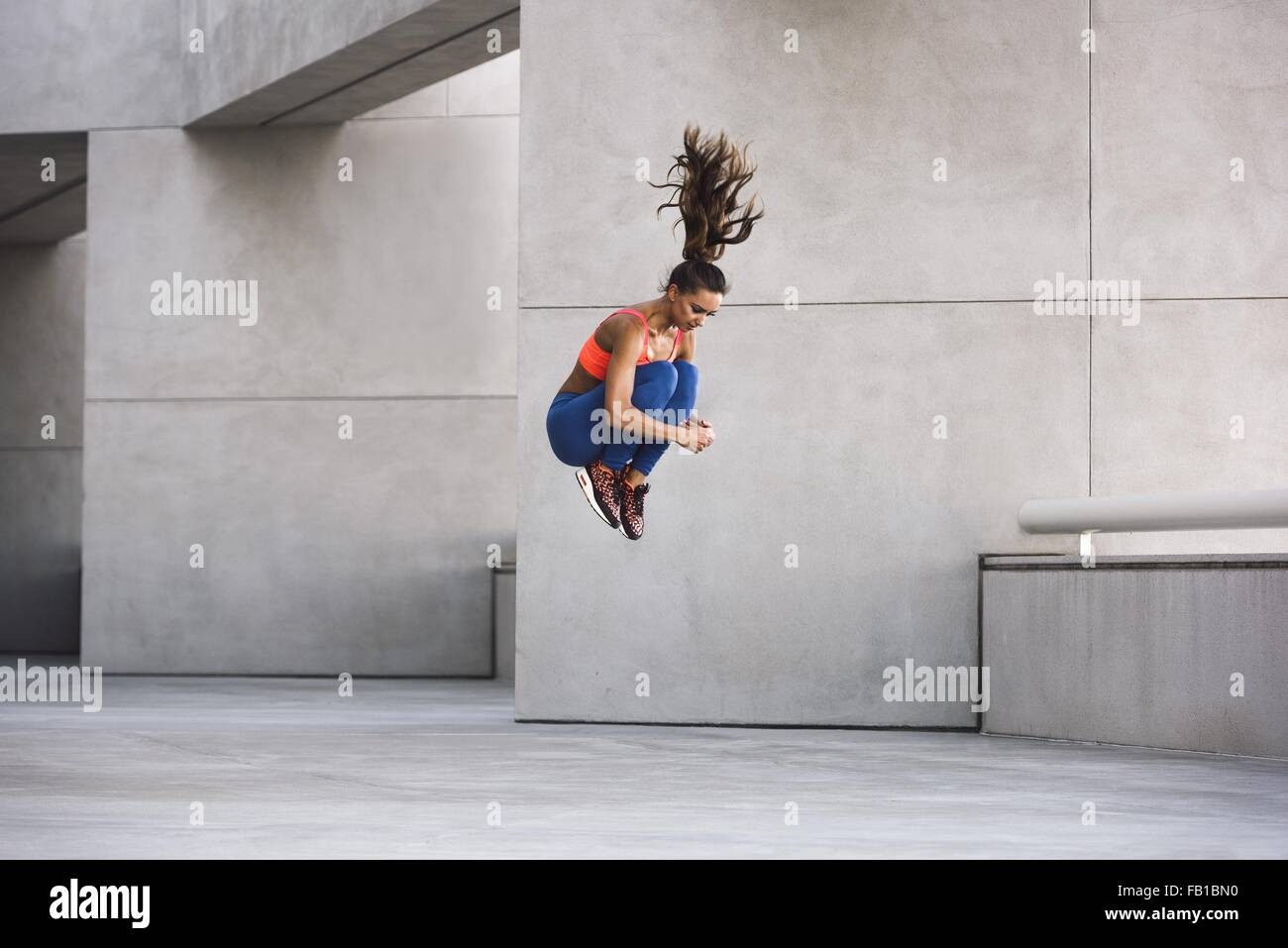 Vista laterale della giovane donna jumping abbracciando le ginocchia a metà in aria Immagini Stock