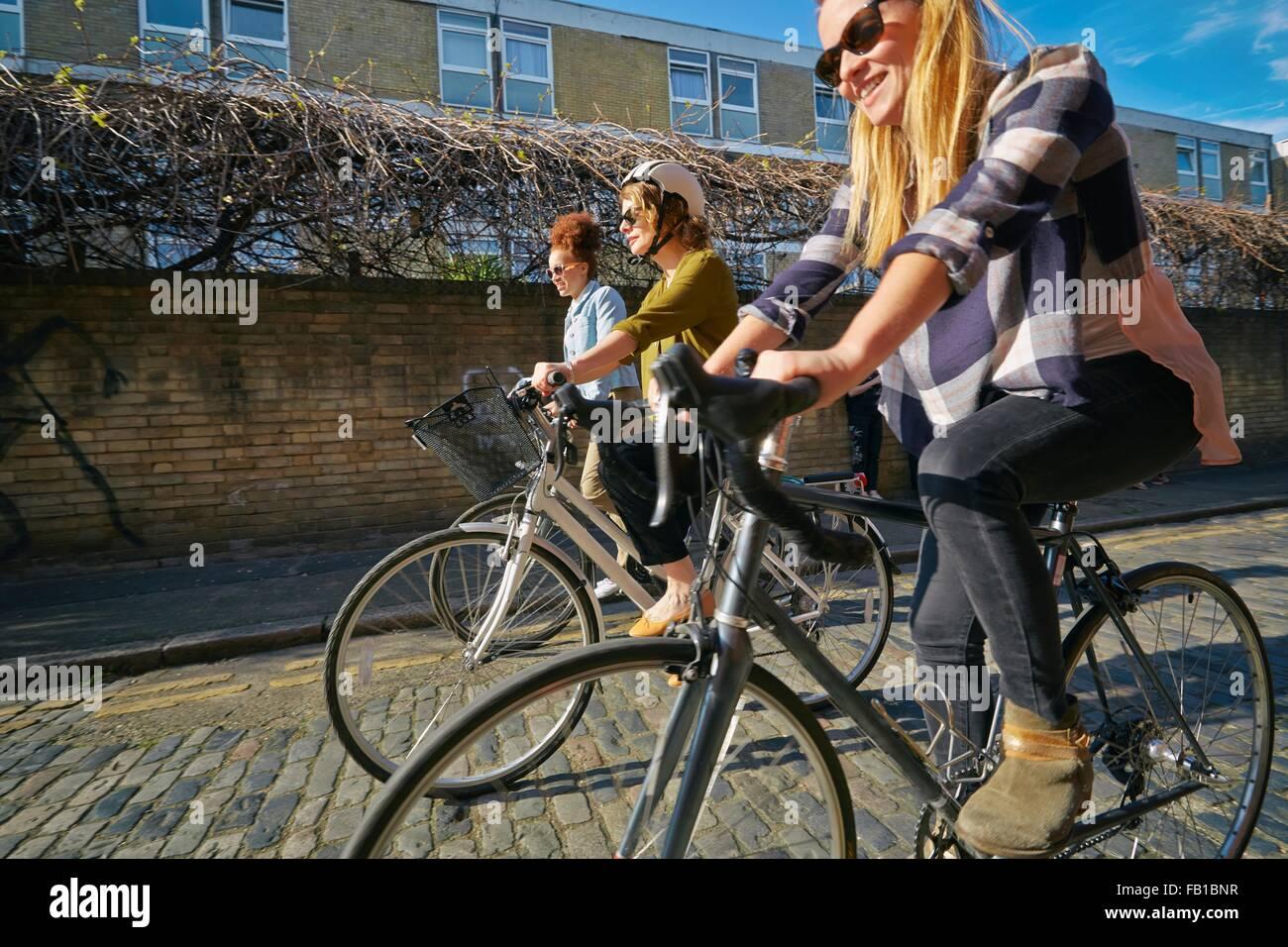 Vista laterale di donne escursioni in bicicletta sulla strada acciottolata Immagini Stock