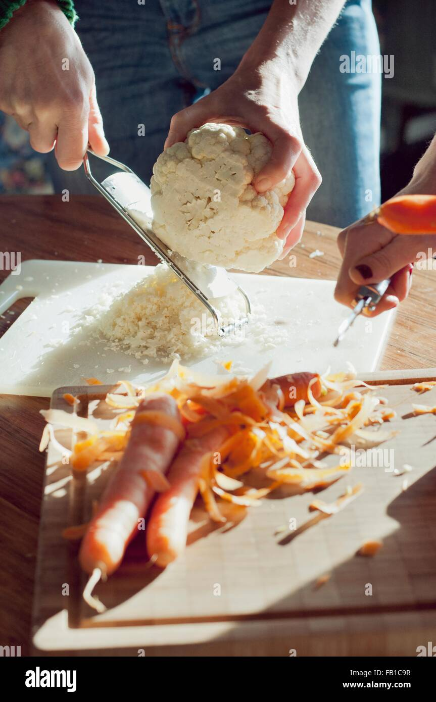Ritagliato colpo di mani femminili per preparare verdure organiche Immagini Stock