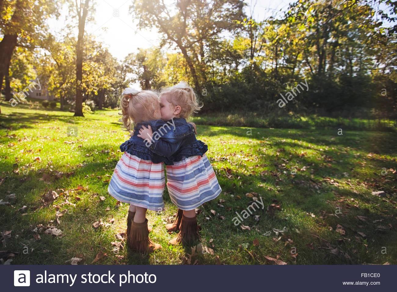 Twin ragazze che indossano abiti di corrispondenza faccia a faccia abbracciando e baciando Immagini Stock