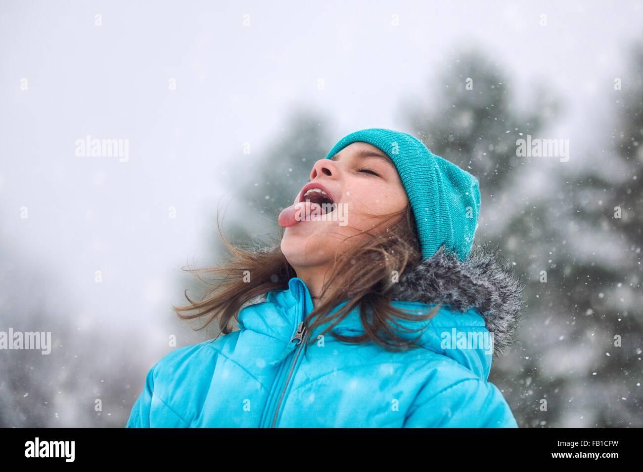 Ragazza guardando in alto, spuntavano lingua cattura i fiocchi di neve Immagini Stock