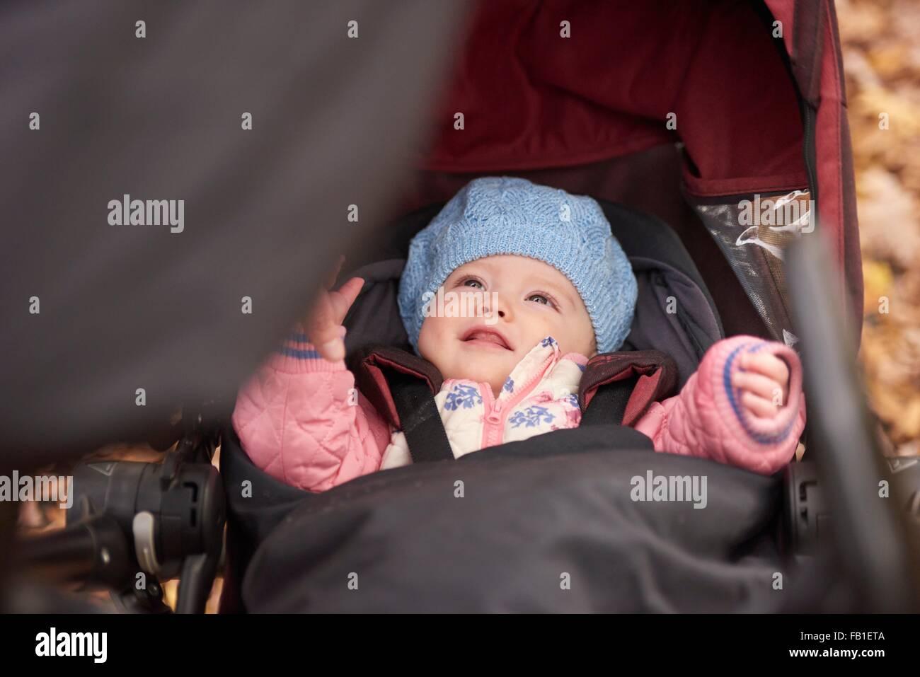 Bambina indossa blue hat cercando da bambino trasporto Immagini Stock