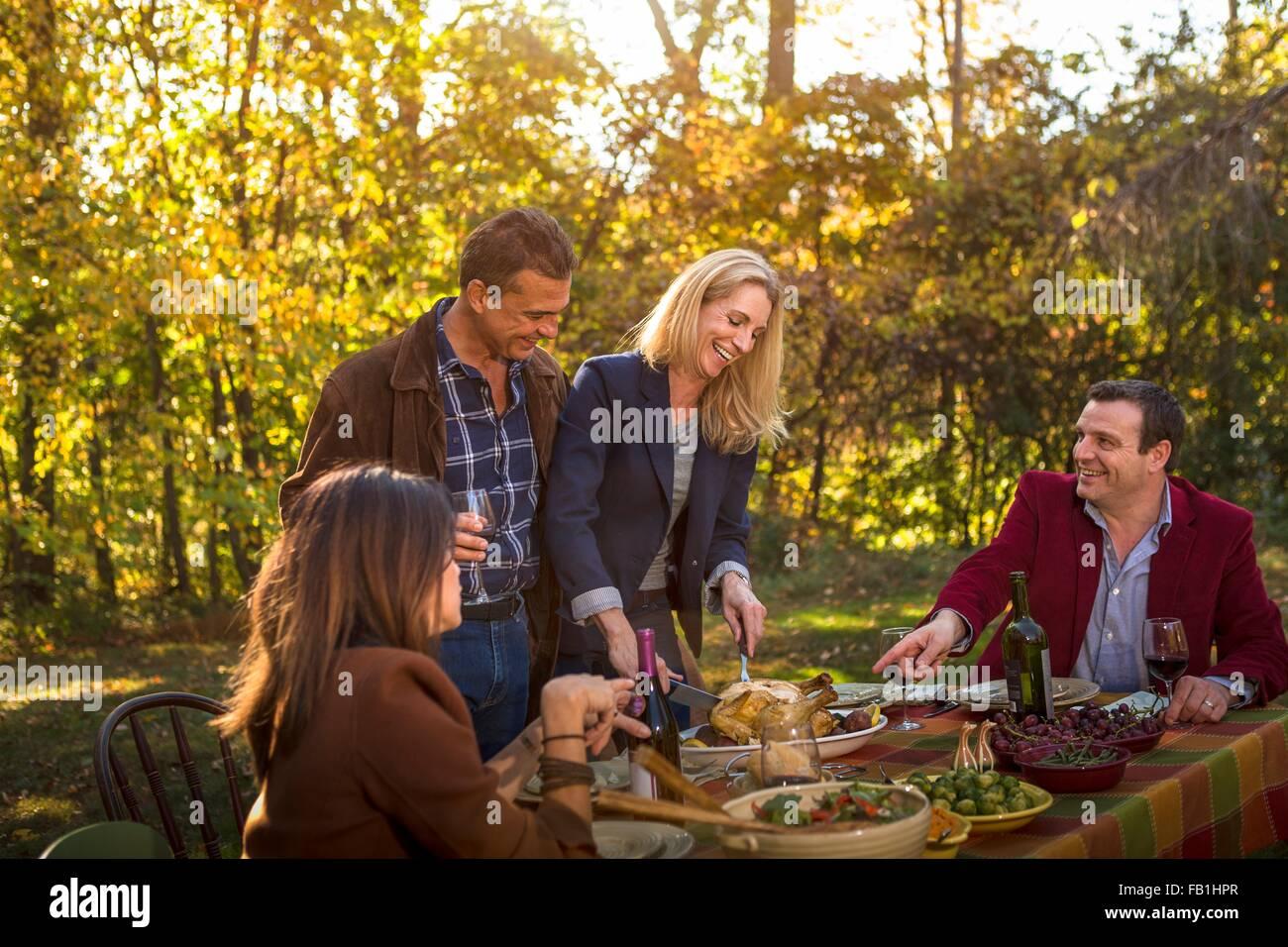 Due coppie mature che serve cena arrosto al party in giardino Immagini Stock