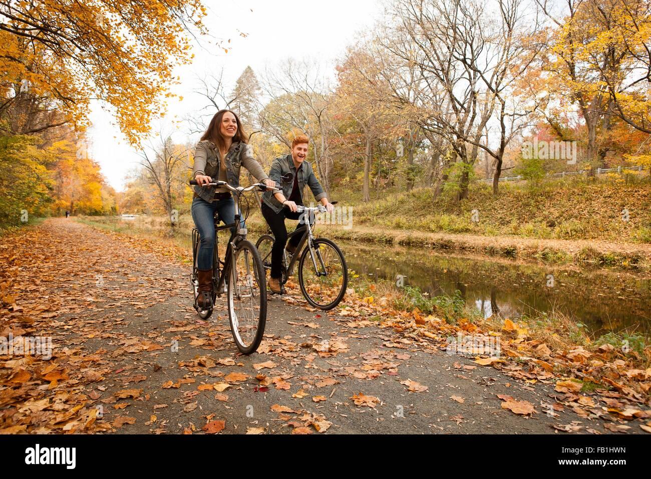 Felice coppia giovane escursioni in bicicletta lungo il fiume in autunno Immagini Stock