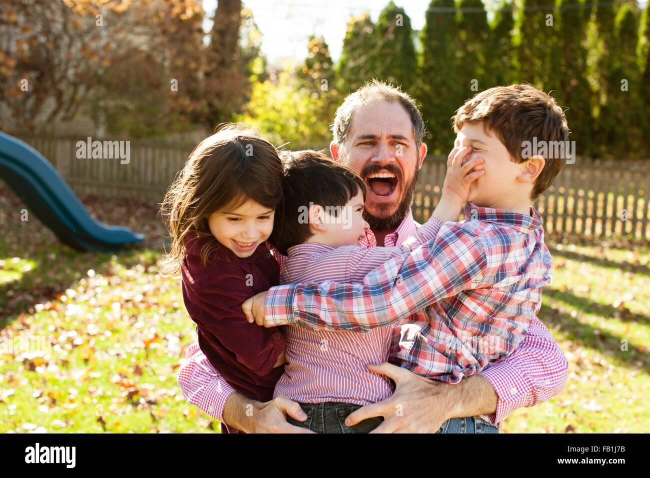 Padre che trasportano bambini allegri nelle sue braccia, con imboccatura aperta cercando sorpreso Immagini Stock