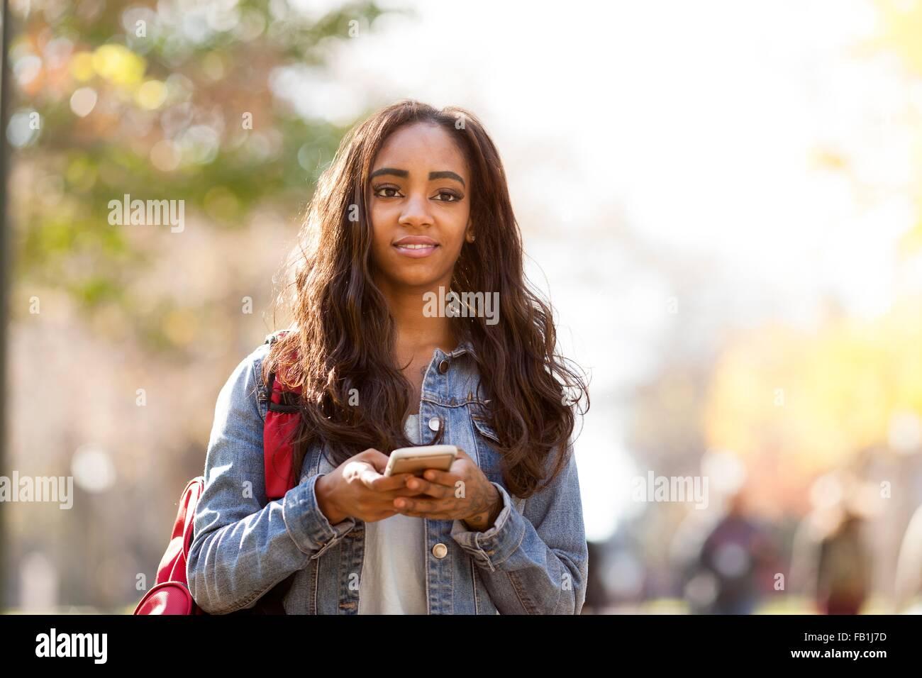 Giovane donna con capelli lunghi marrone indossando giacca denim smartphone tenendo lo sguardo lontano sorridente Immagini Stock