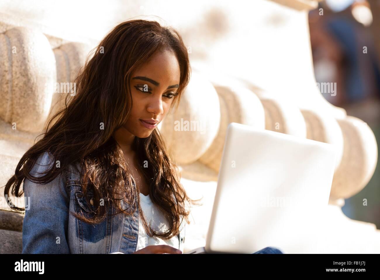 Giovane donna seduta appoggiata contro la scultura in pietra guardando verso il basso utilizzando il computer portatile Immagini Stock