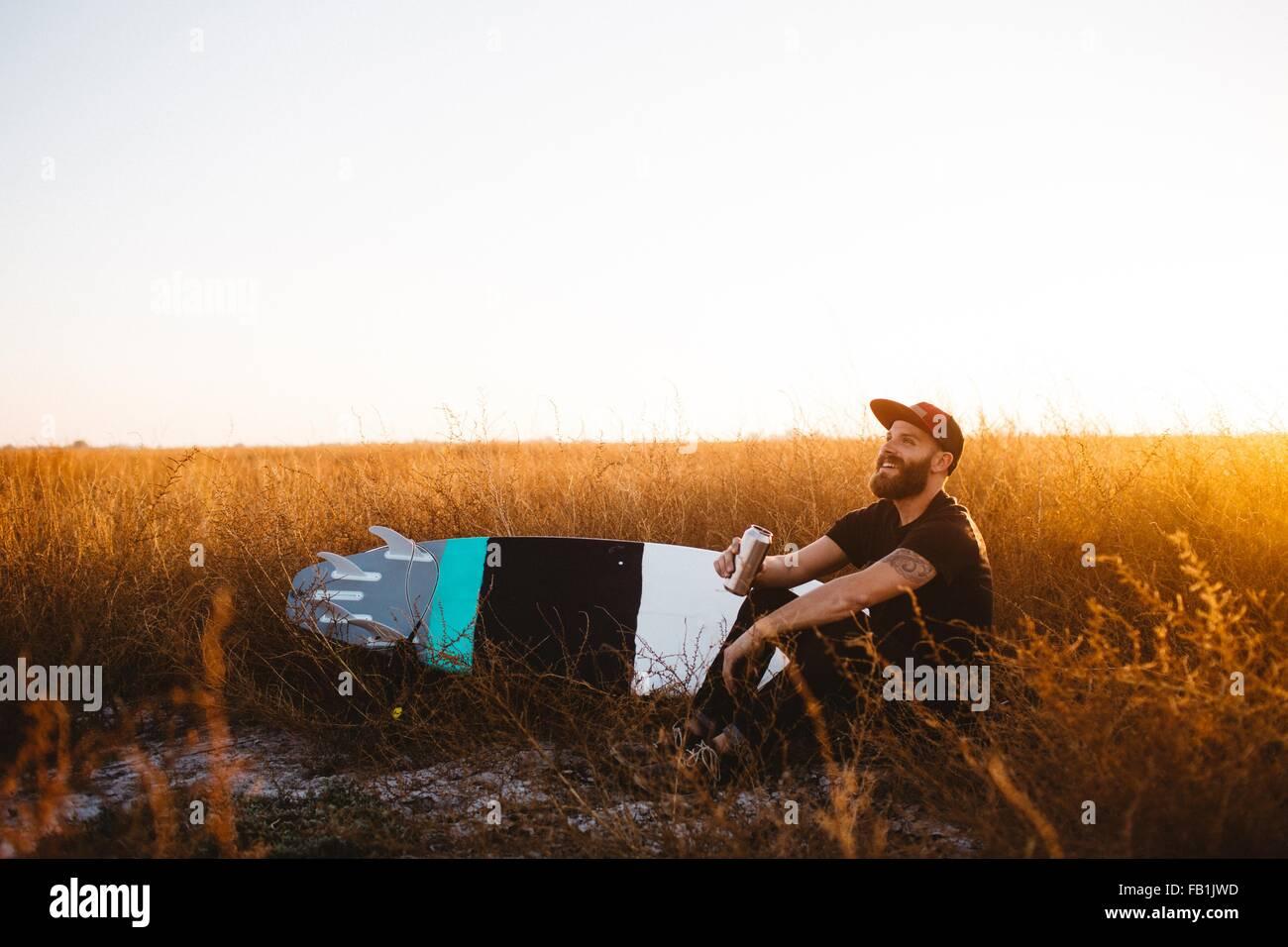 Surfista maschio a bere birra nel campo di erba lunga al tramonto, San Luis Obispo, California, Stati Uniti d'America Immagini Stock