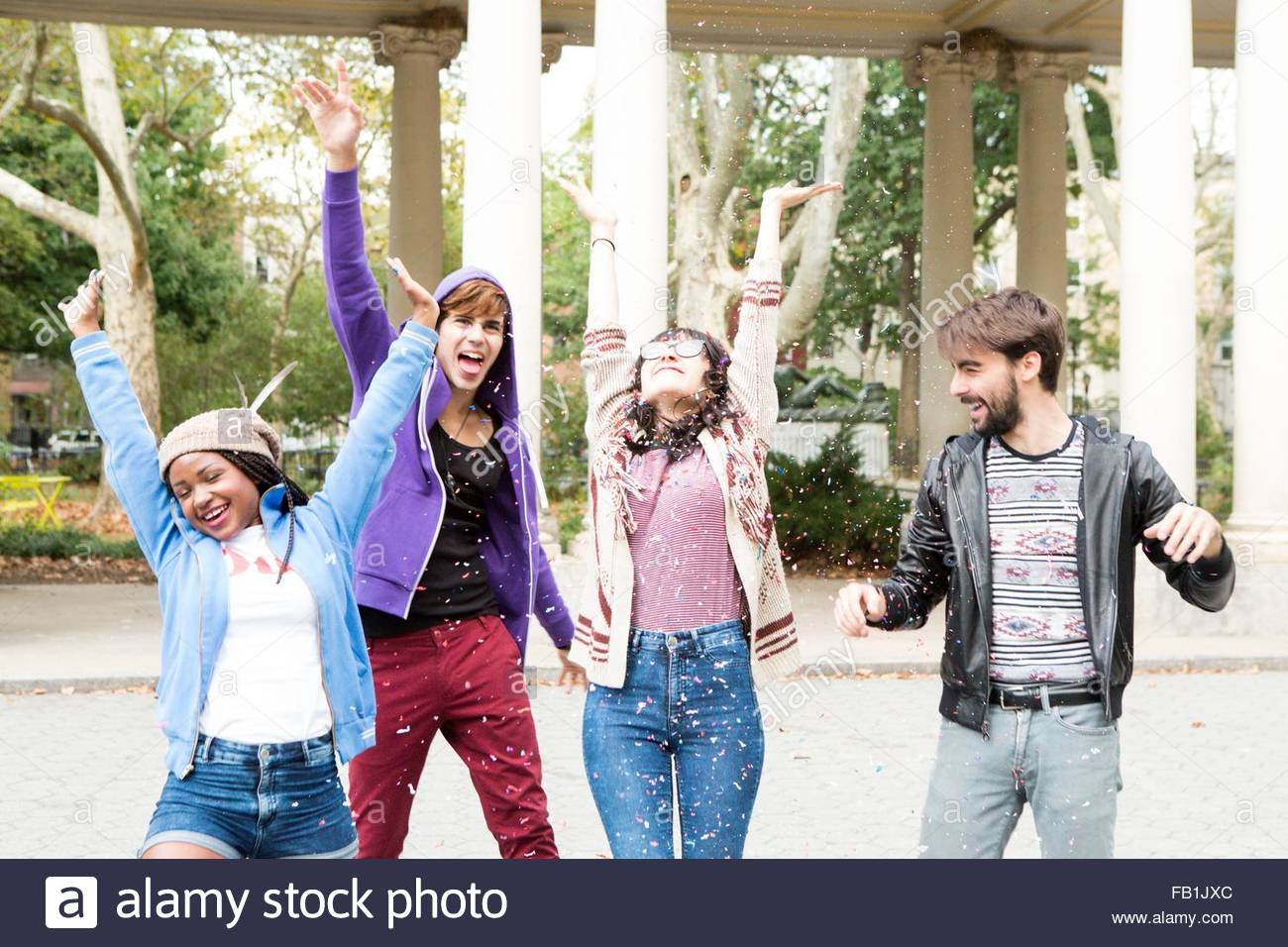 Quattro giovani amici adulti gettando coriandoli nel parco, Brooklyn, New York, Stati Uniti d'America Immagini Stock