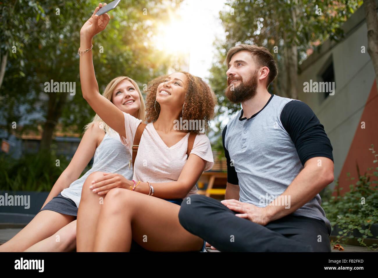 Tre giovani amici prendendo un selfie con cellulare. Gruppo multirazziale di giovani divertirsi insieme mentre seduti Immagini Stock