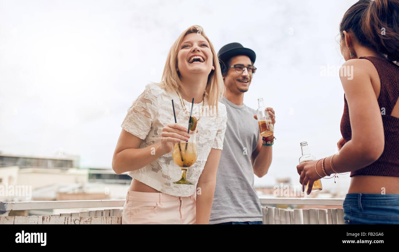 Ritratto di Allegro giovane donna godendo il partito con i suoi amici. Giovani divertendosi al partito sul tetto. Immagini Stock
