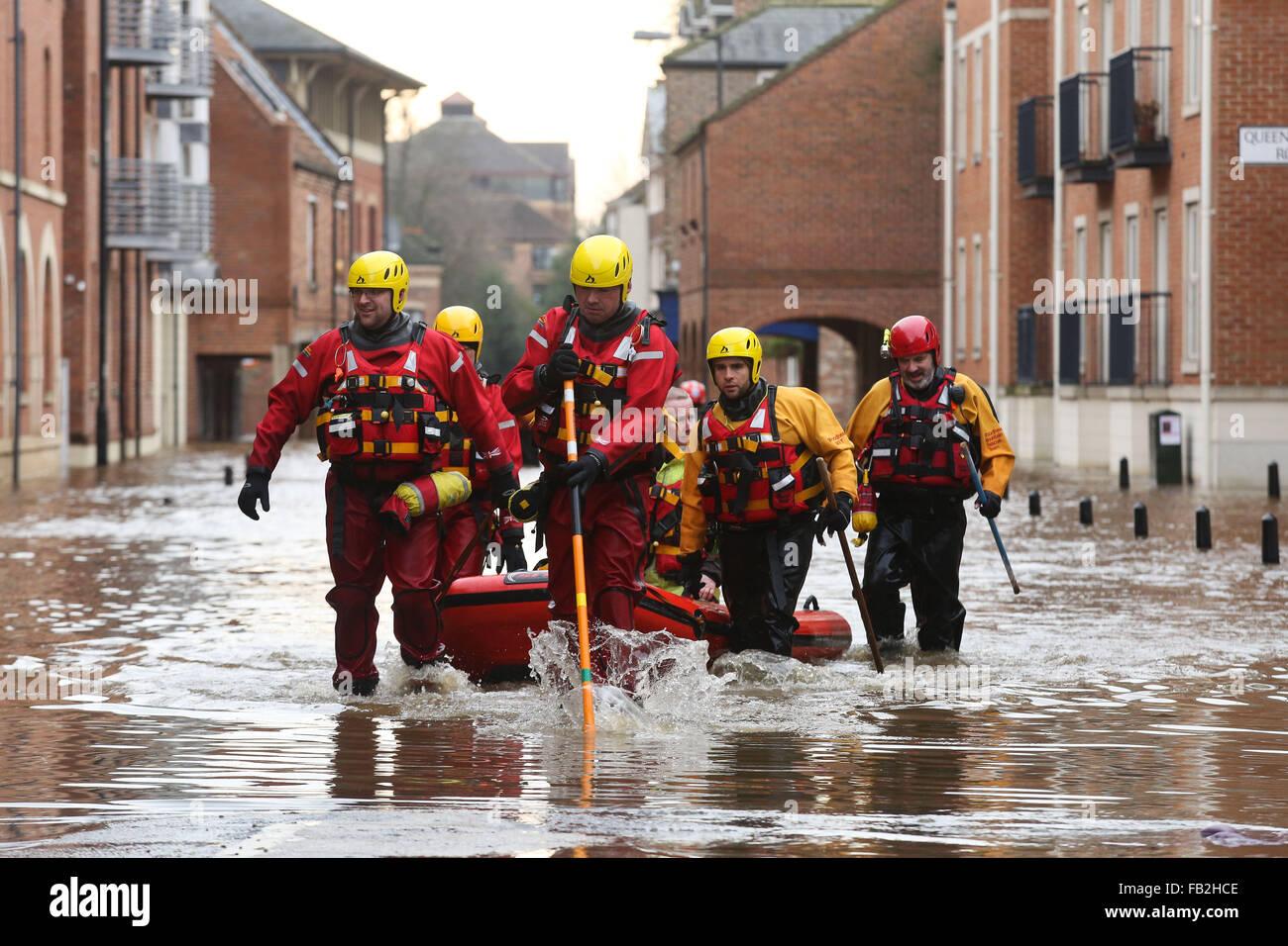 Gli operatori di soccorso wade attraverso alta acqua di inondazione in York, nello Yorkshire, Regno Unito, sia dopo Immagini Stock
