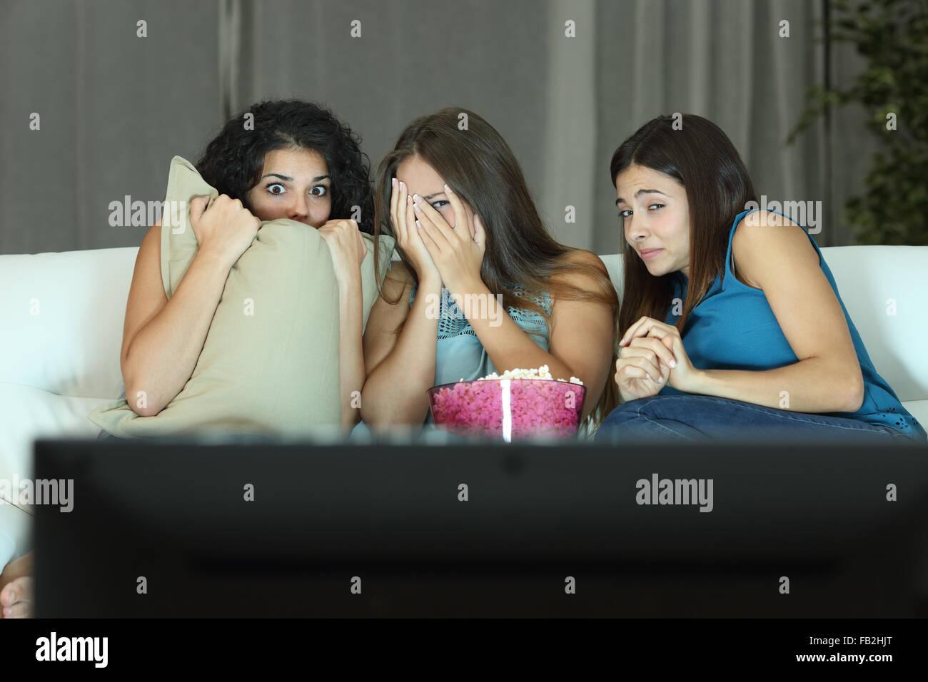 Le ragazze di guardare un film del terrore in tv seduti su un lettino a casa Immagini Stock