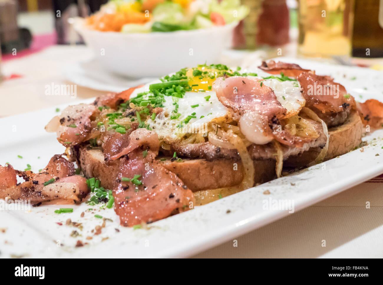 Bauerntoast preparati con carne, bacon, pane e uova cotte in cima, piatto tradizionale in Alto Adige e Sud Tirolo. Immagini Stock