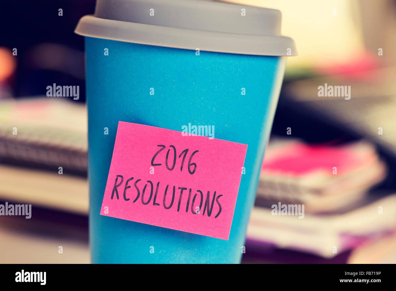 Primo piano di una rosa una nota adesiva con il testo delle risoluzioni 2016 in una tazza di colore blu su una scrivania Immagini Stock