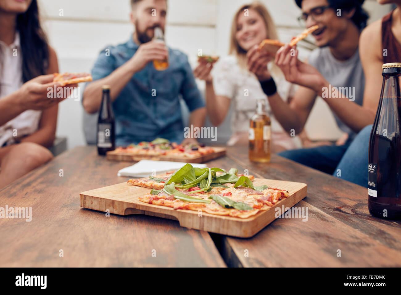 Immagine ravvicinata di pizza sul piatto di legno con persone di mangiare e di bere in background. Gruppo di amici Immagini Stock