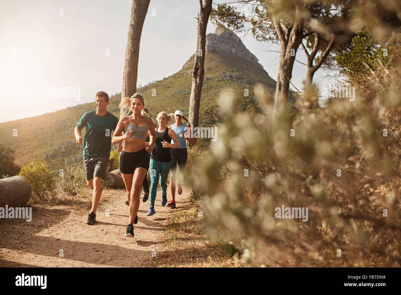 Un gruppo di giovani adulti e di formazione in esecuzione insieme attraverso sentieri sulla collina all'aperto Immagini Stock