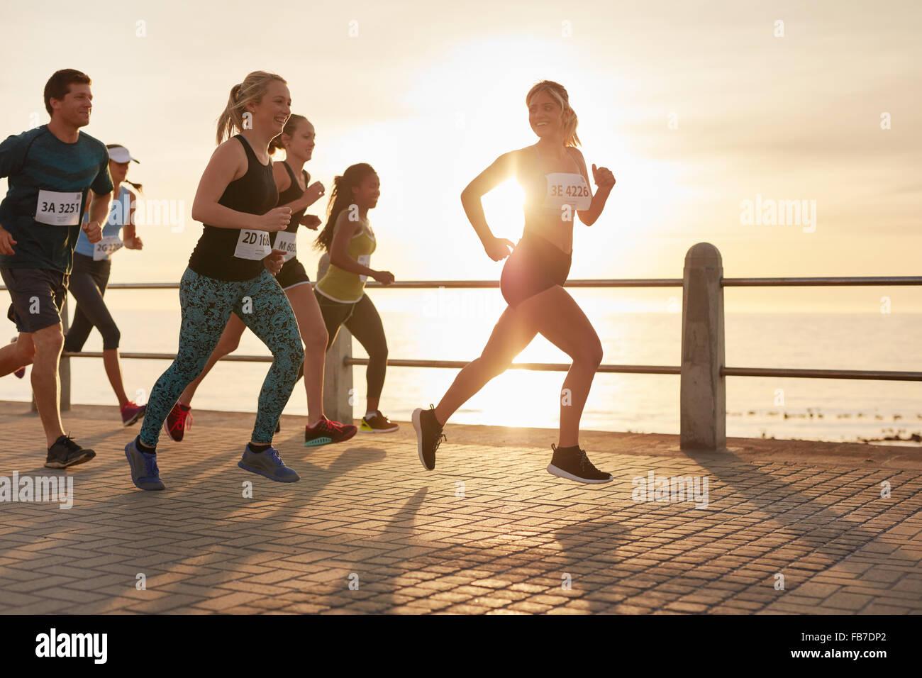 Montare i giovani in esecuzione su strada con il mare. Guide di scorrimento per competere in una gara di maratona Immagini Stock