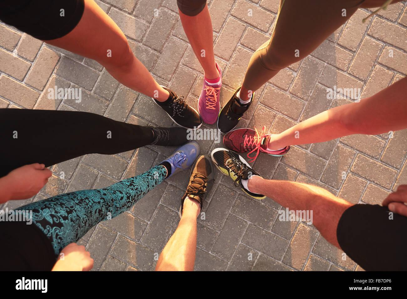Le gambe degli atleti di indossare calzature sportive in un cerchio. Vista superiore di pattini in piedi insieme. Immagini Stock