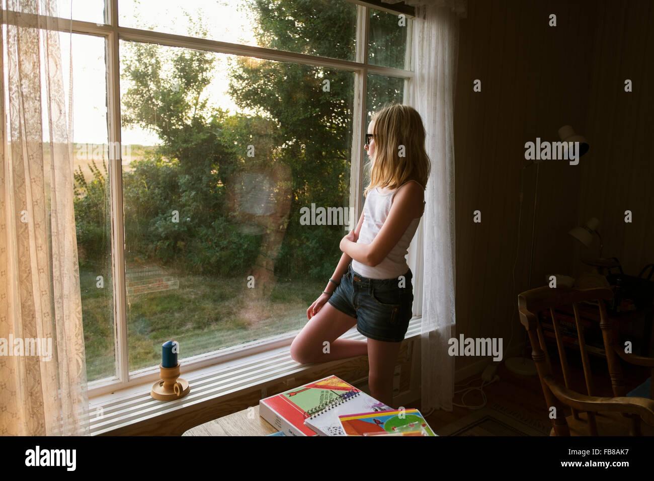 La Svezia, Skane, Vejbystrand, ragazza (10-11) guardando anche se finestra Immagini Stock