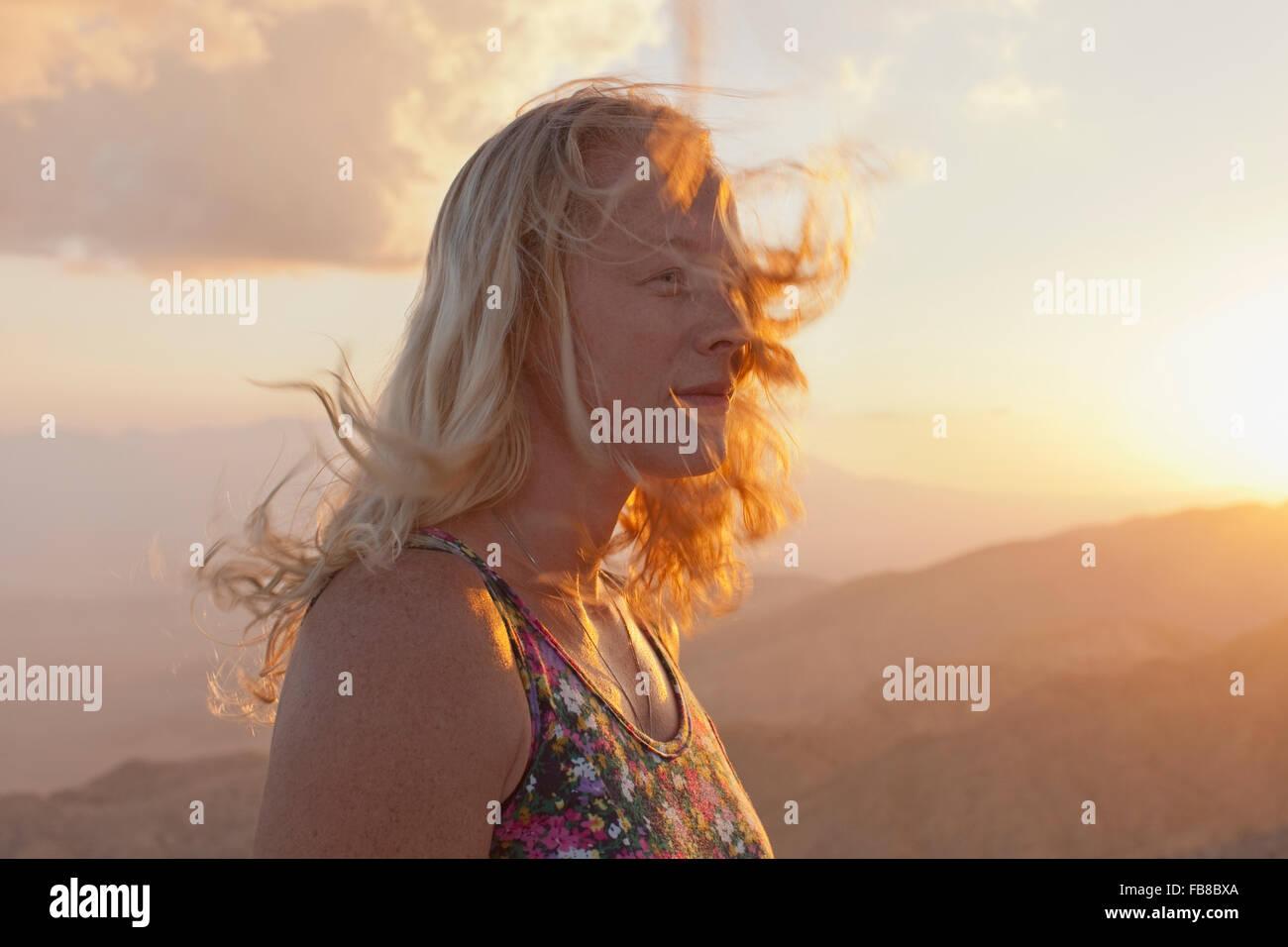 Stati Uniti, California, Joshua Tree National Park, il turista femminile relax nel paesaggio di montagna al tramonto Immagini Stock