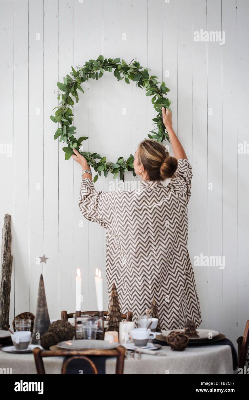 La Svezia, Donna appeso ghirlanda di Natale sulla parete Immagini Stock