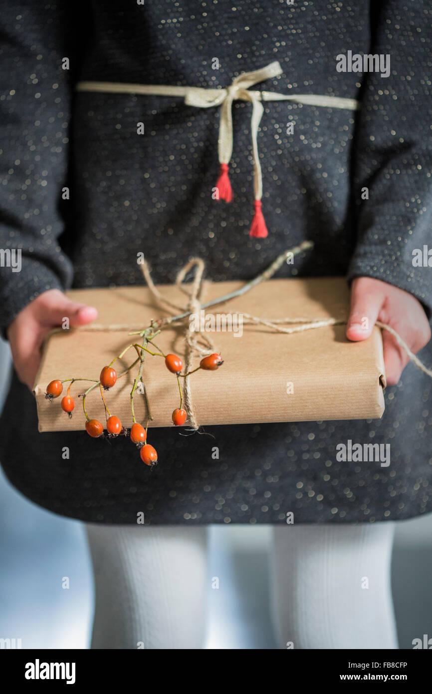 La Svezia, ragazza (6-7) azienda avvolto regalo di Natale Immagini Stock