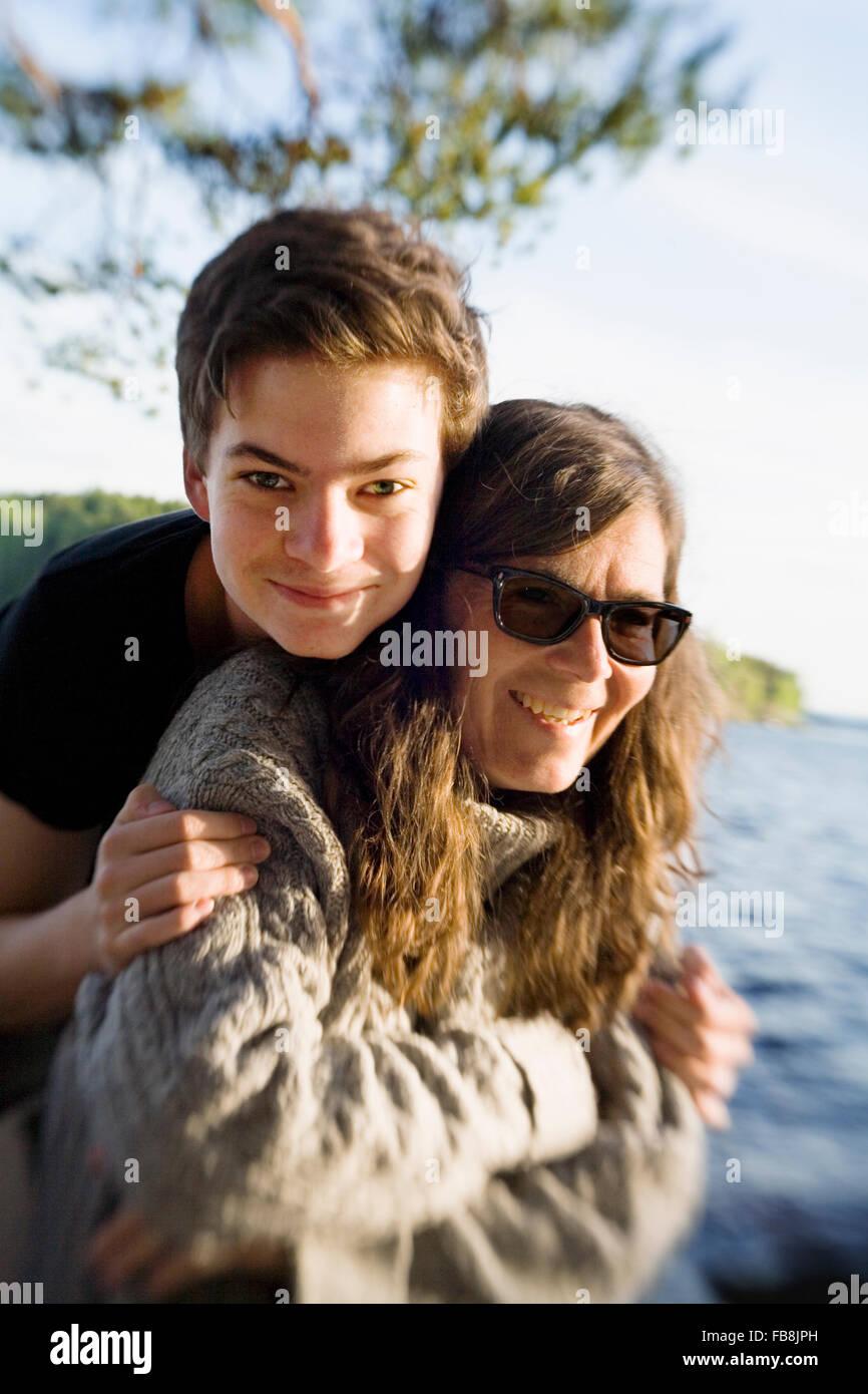 La Svezia, Dalarna, Ritratto di ragazzo adolescente (14-15) con la sua mamma sul lungolago Immagini Stock