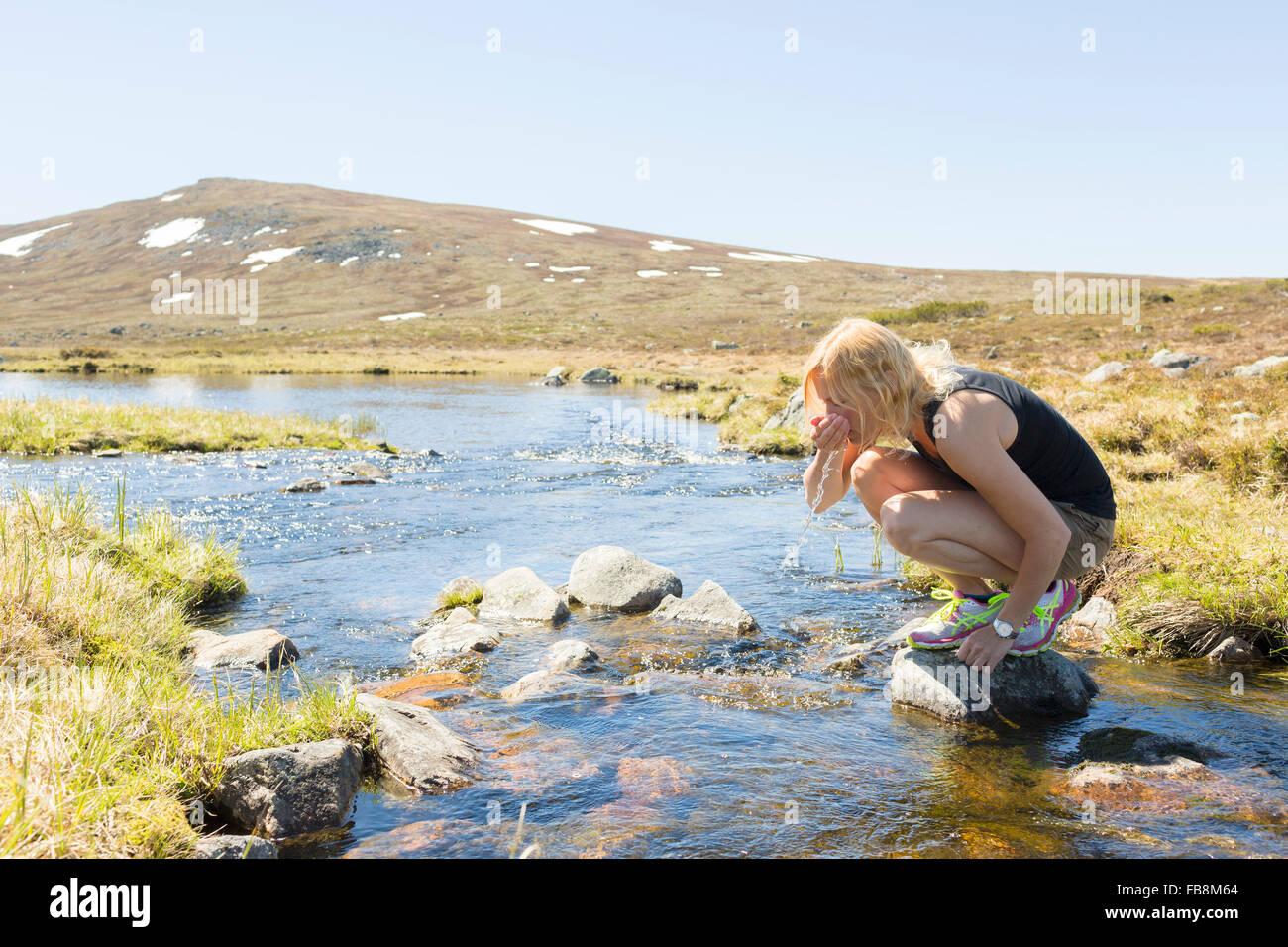 La Svezia, Dalarna, Grovelsjon, donna di bere acqua dal fiume di montagna Immagini Stock