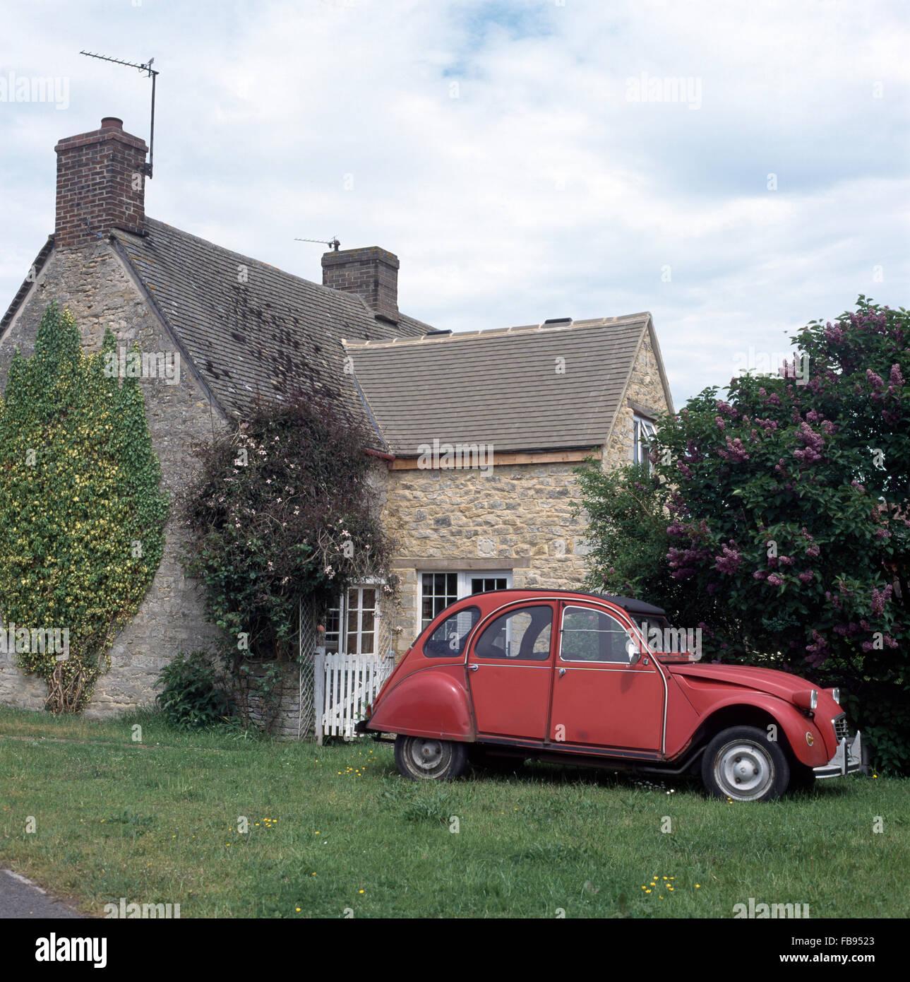 Vintage red Citroen 2CV sull'erba a fianco di pietra del paese cottage con un ben costruito estensione Immagini Stock