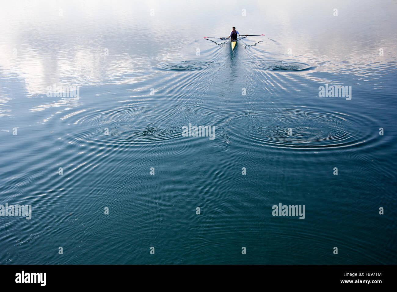 Giovane uomo in una barca, canottaggio sul lago tranquillo Immagini Stock
