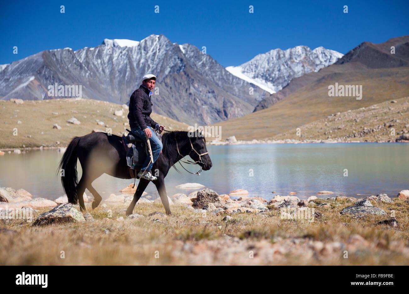 Tsaganaa, una guida e herder equitazione nei pressi di un lago glaciale in remoto Turgen Kharkhiraa National Park, Immagini Stock