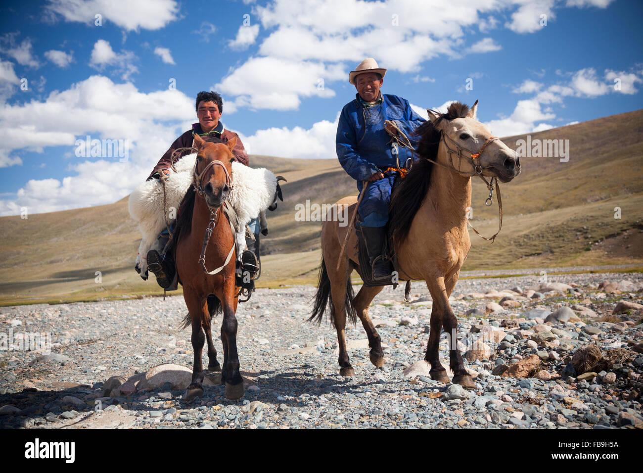 Nomads tornando al campo dopo la raccolta di una pecora di runaway in Kharkhiraa Turgen Parco Nazionale. Immagini Stock