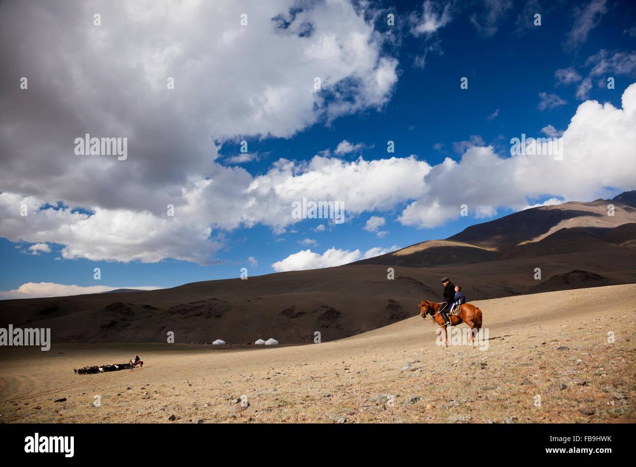 Un herder veglia sulla sua animali in Tsaast Uul valley, Mongolia occidentale. Immagini Stock