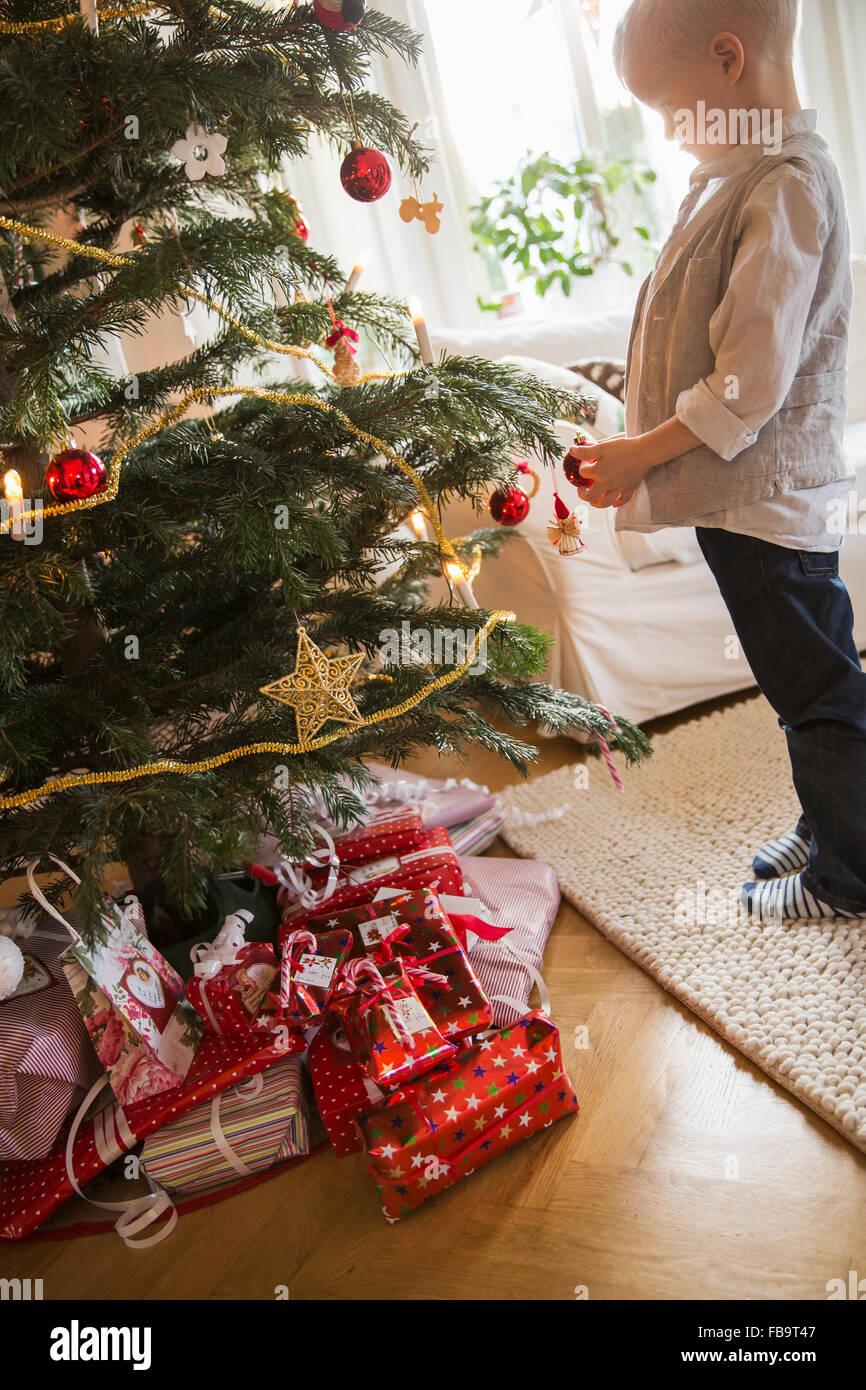 La Svezia, il piccolo ragazzo biondo (4-5) in piedi accanto ad albero di Natale Immagini Stock