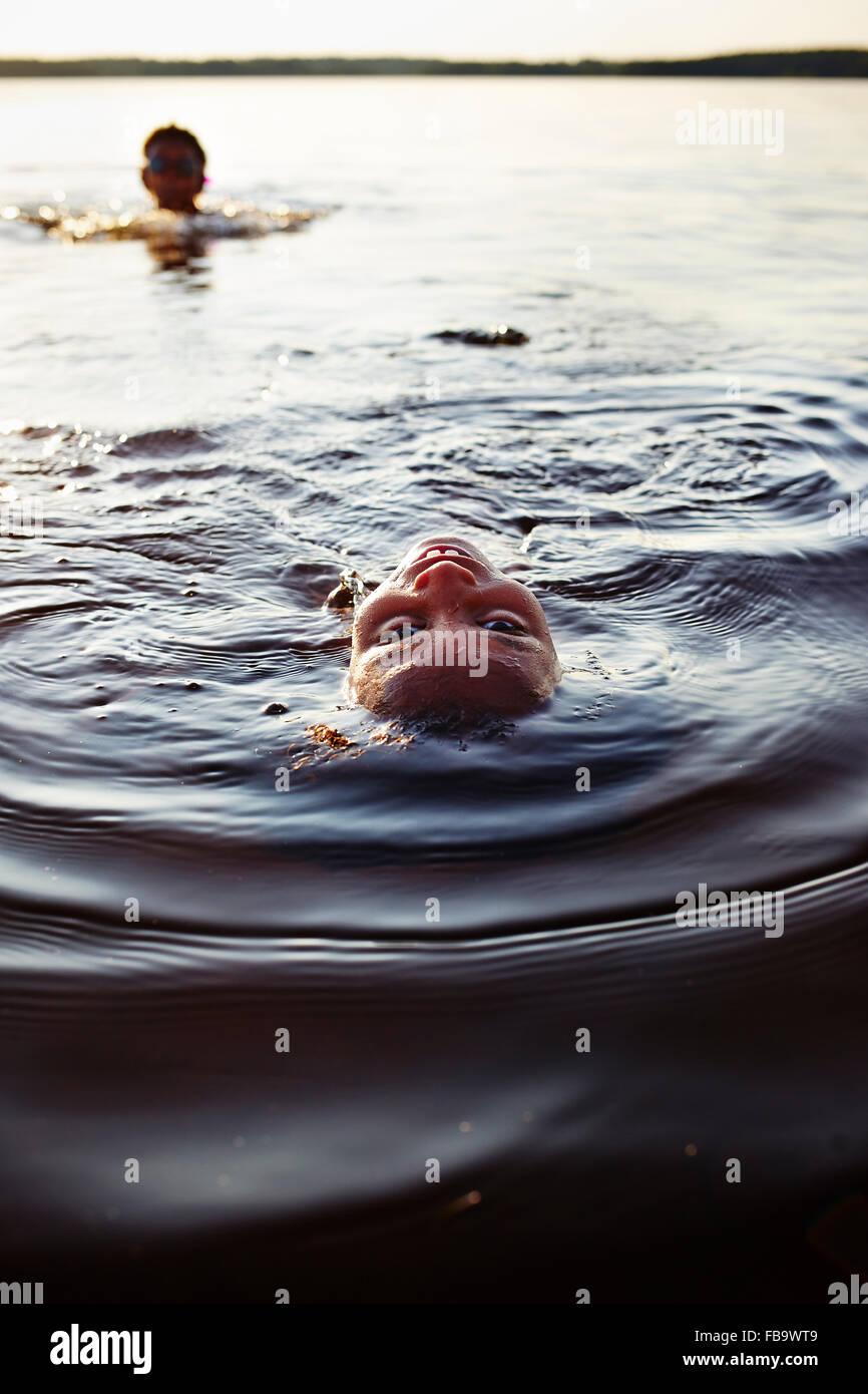 La Svezia, Vastra Gotaland, Skagern, Bambini (6-7, 10-11) nuotare nel lago Immagini Stock
