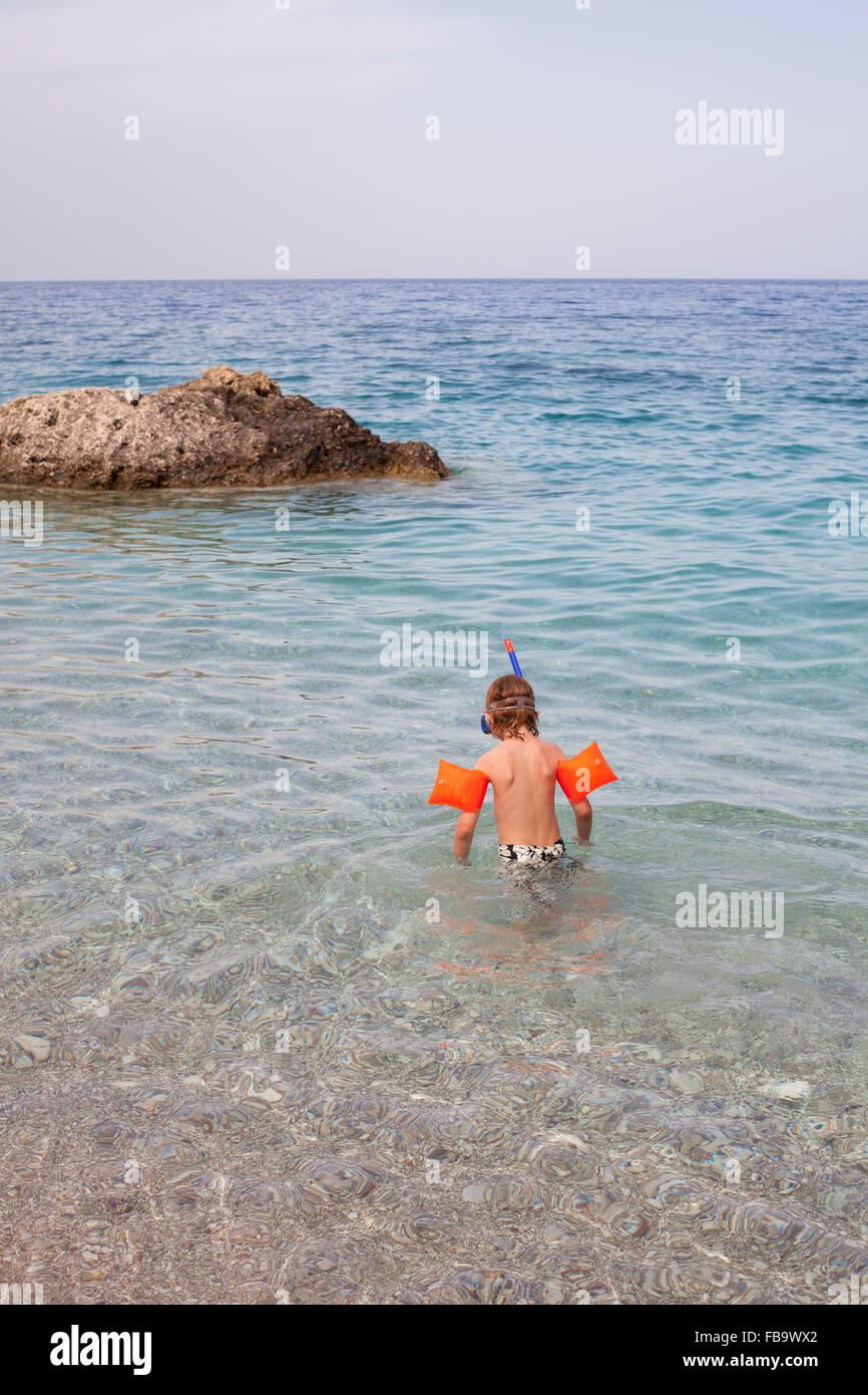 Grecia KARPATHOS, Amopi, ragazzo (8-9) guardando l'acqua Immagini Stock
