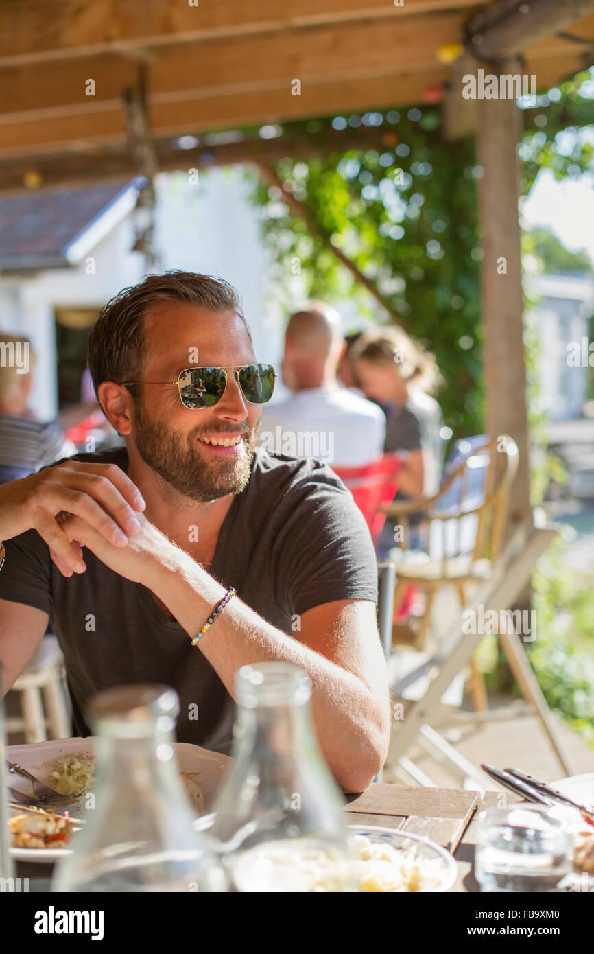 La Svezia, Skane, uomo maturo in occhiali da sole di mangiare il pranzo Immagini Stock