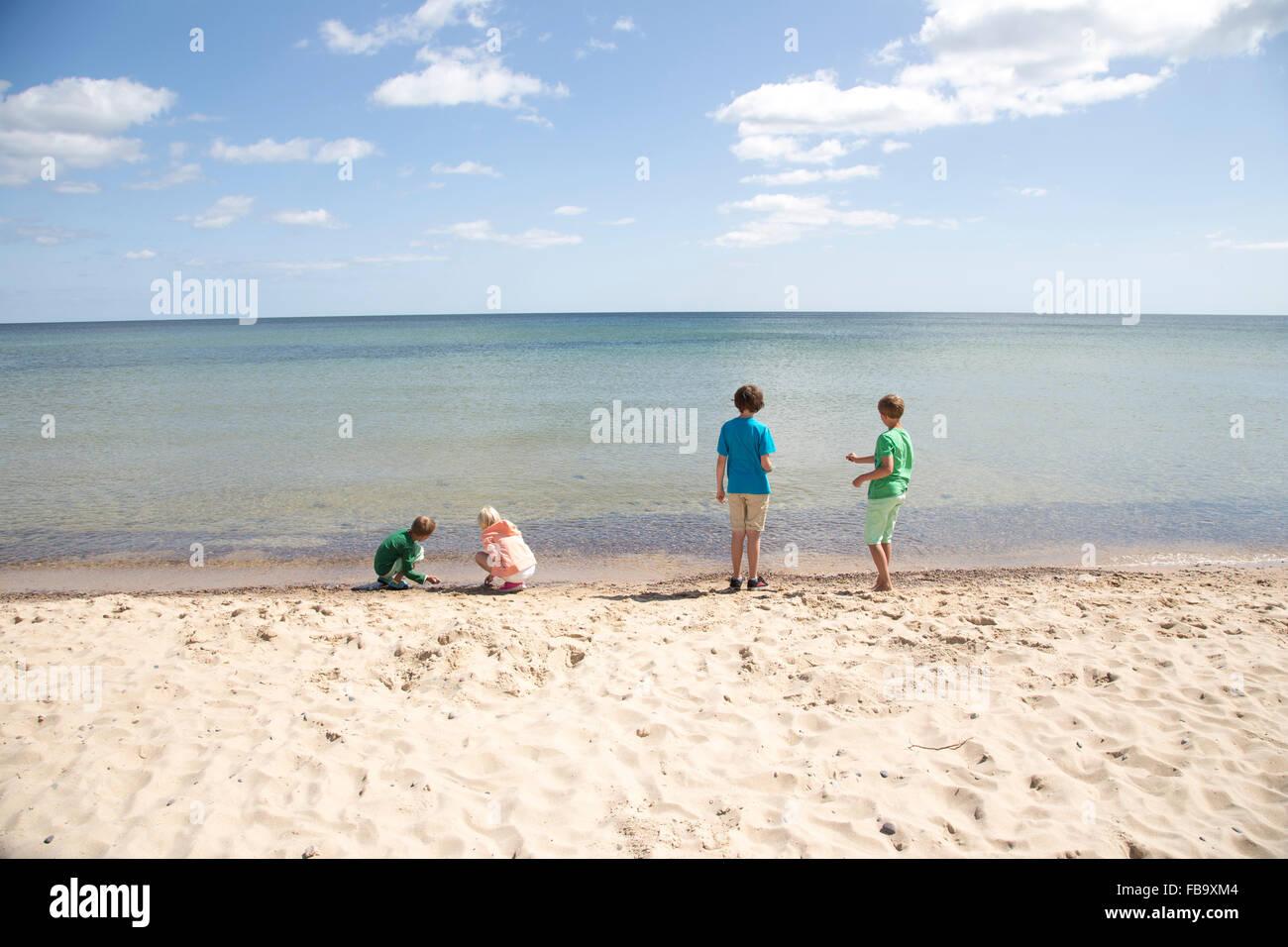 La Svezia, Skane, Osterlen, Stenshuvud, Bambini (8-9, 10-11, 12-13) giocando sulla spiaggia Foto Stock