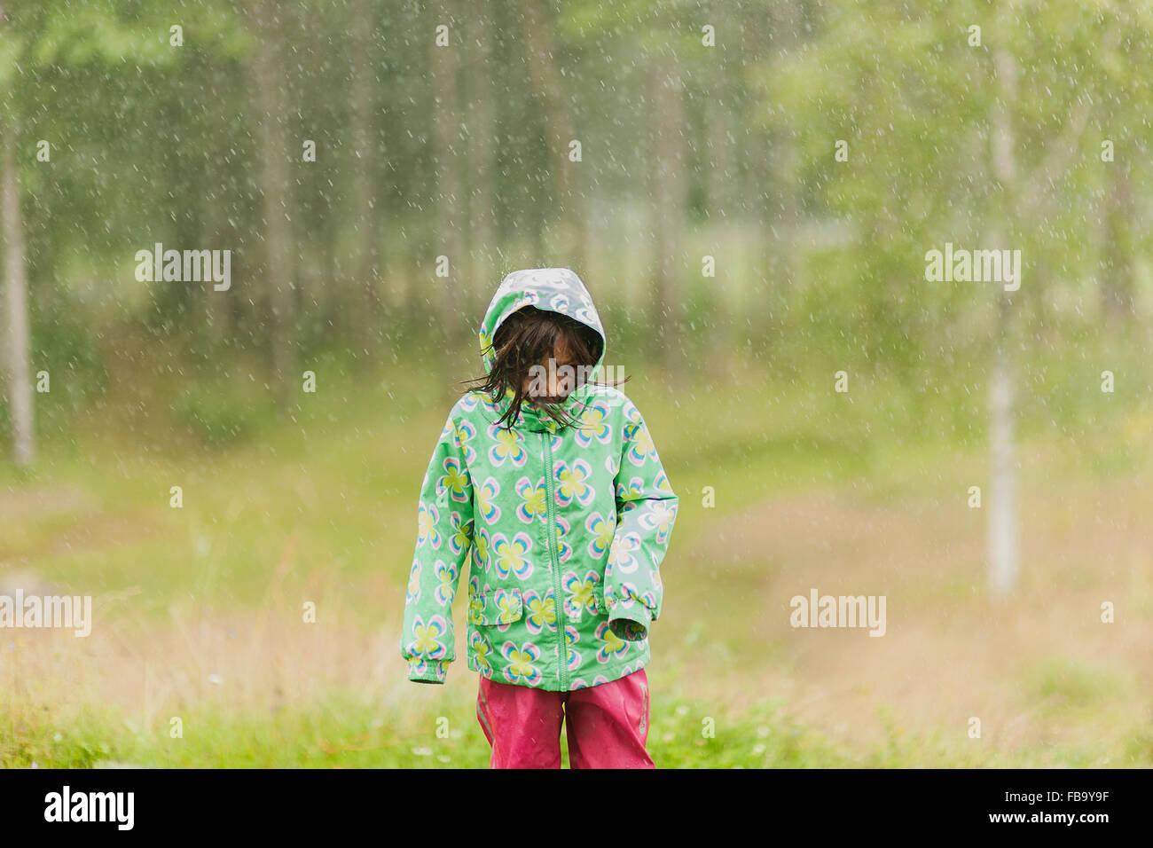 La Svezia, Vastmanland, Bergslagen, ragazza (4-5) in esecuzione in caso di pioggia Immagini Stock