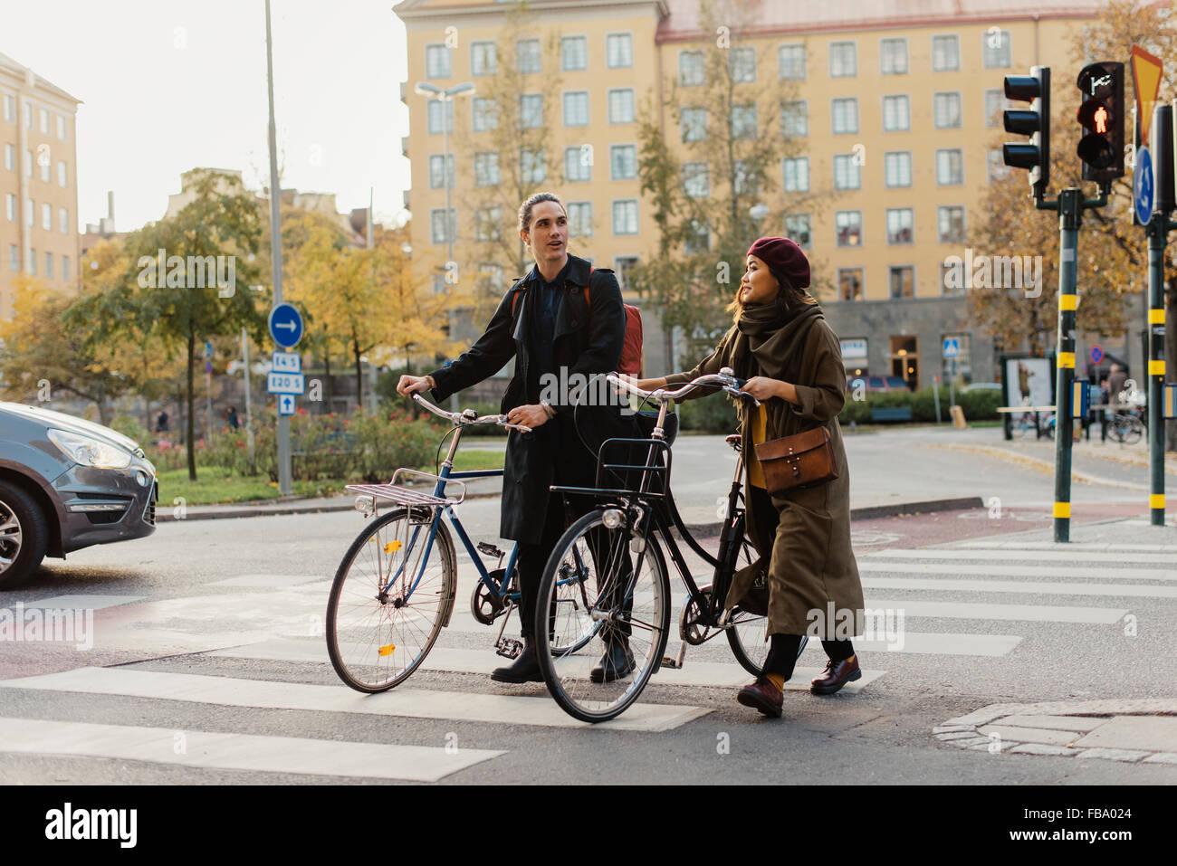 La Svezia, Uppland, Stoccolma, Vasastan, Vanadisplan, due giovani con le biciclette passeggiate attraverso le strisce Immagini Stock