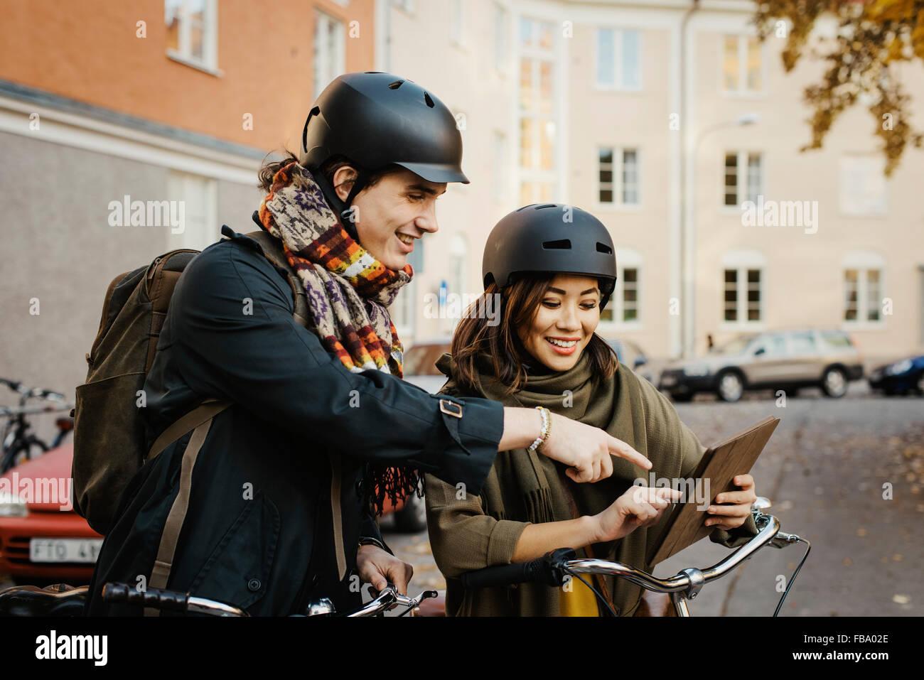 La Svezia, Uppland, Stoccolma, Vasastan, Rodabergsbrinken, due giovani guardando digitale compressa sorridente Foto Stock