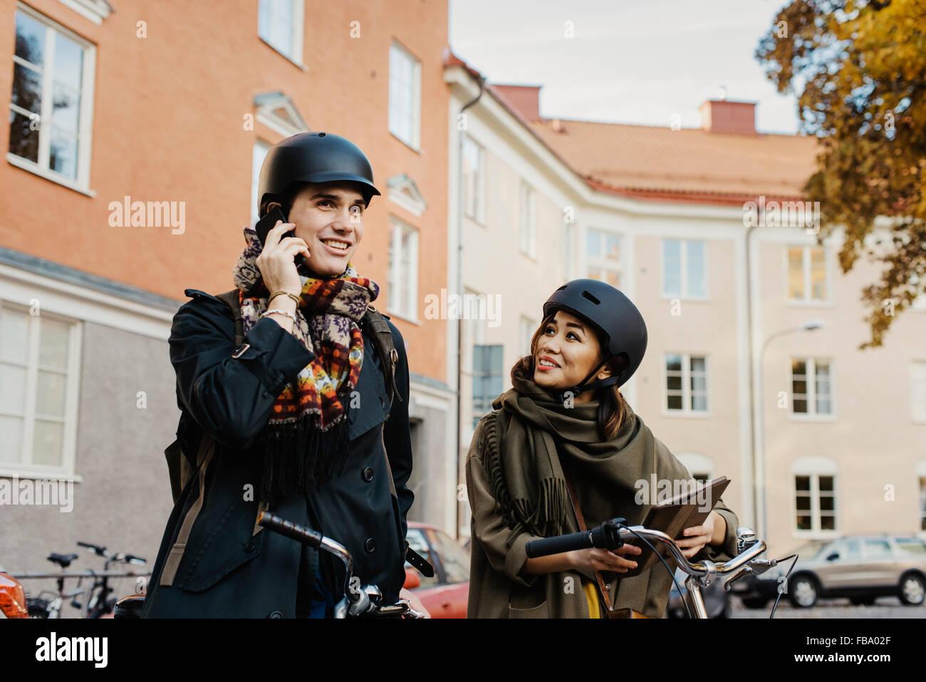 La Svezia, Uppland, Stoccolma, Vasastan, Rodabergsbrinken, due persone in piedi con le biciclette all'aperto Immagini Stock