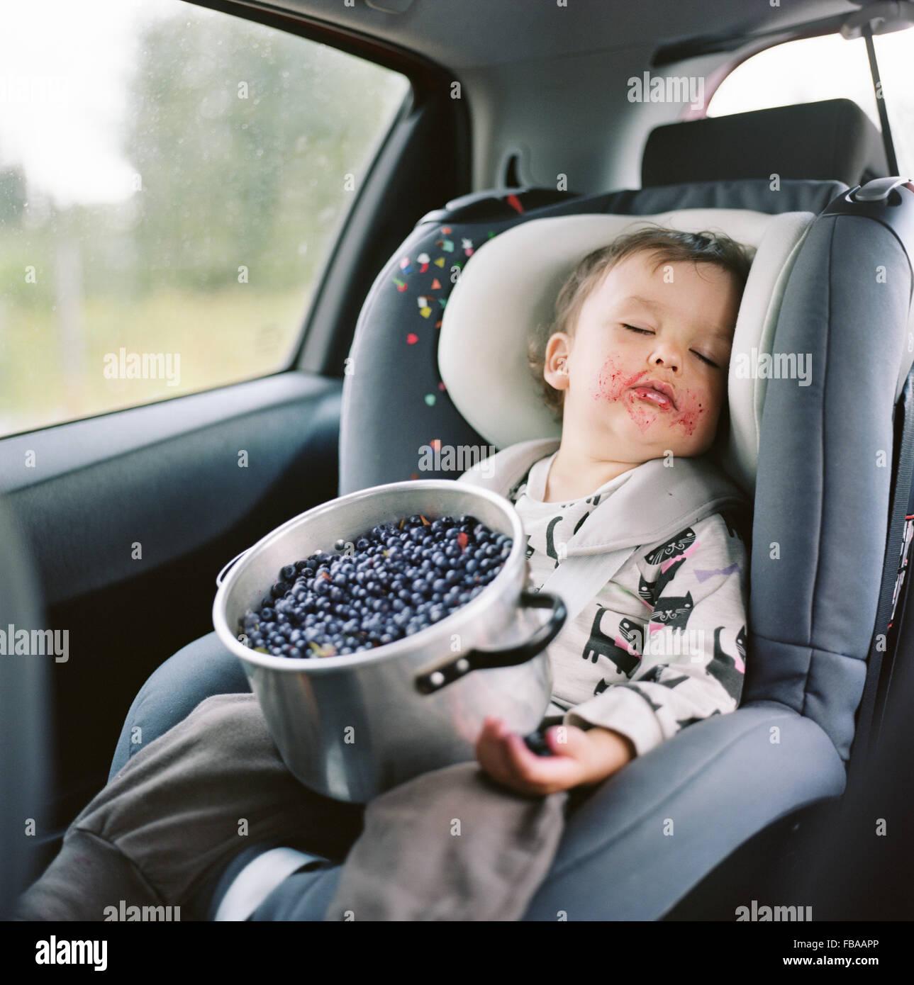Finlandia, Uusimaa, Lapinjarvi, Ritratto di una ragazza (2-3) dormire nel sedile auto con pentola piena di mirtilli Immagini Stock