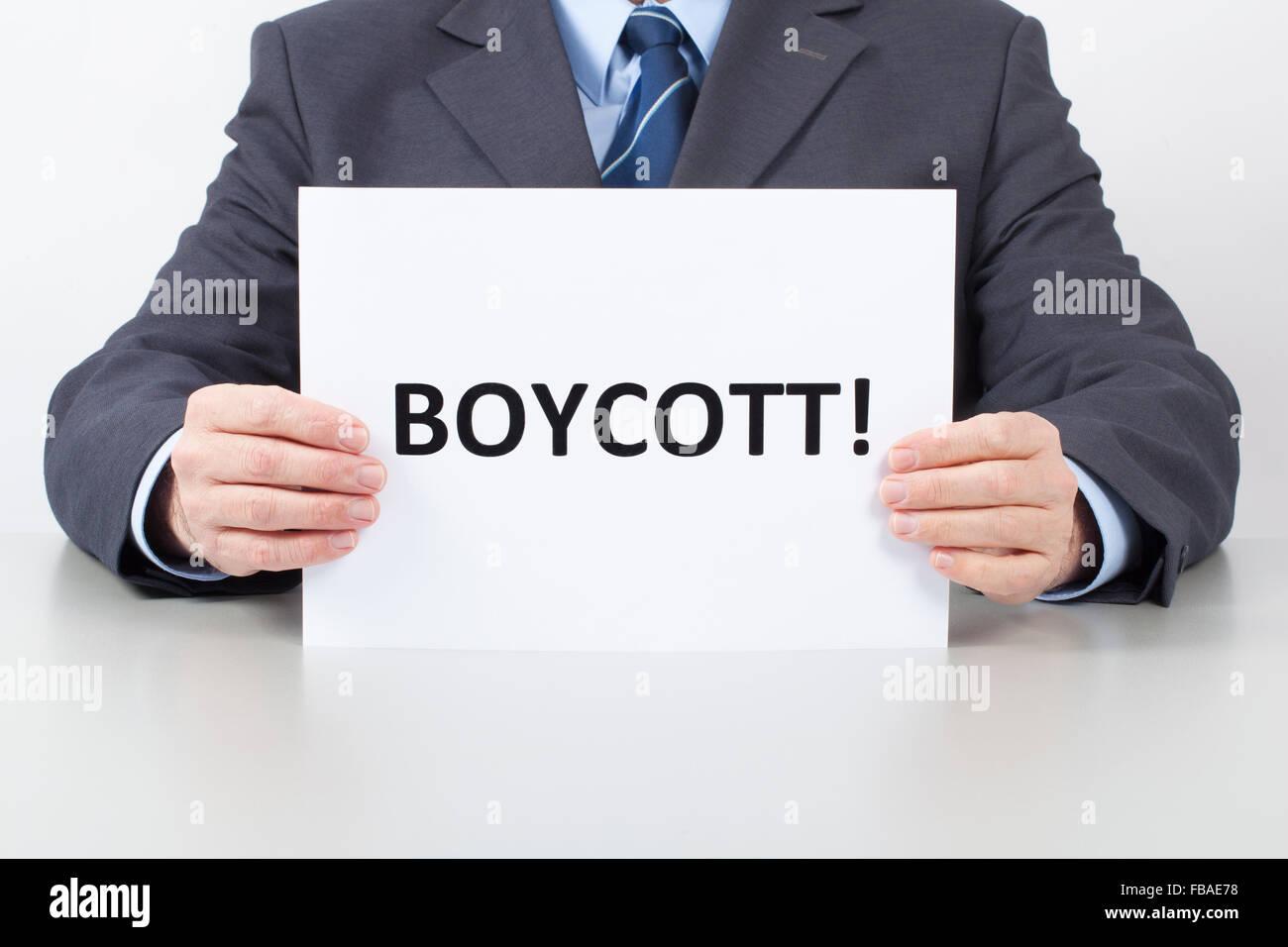 Uomo in tuta seduti dietro un tavolo per ufficio e trattiene un foglio bianco con il boicottaggio di testo nelle Immagini Stock