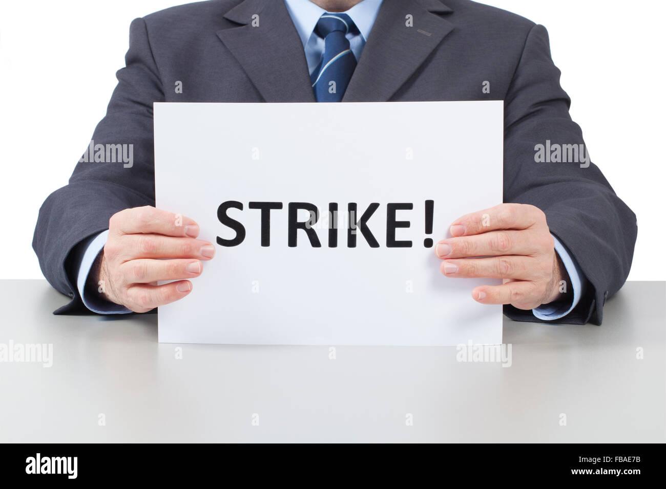 Uomo seduto dietro un tavolo per ufficio e trattiene un foglio bianco con testo sciopero nelle sue mani. Immagini Stock