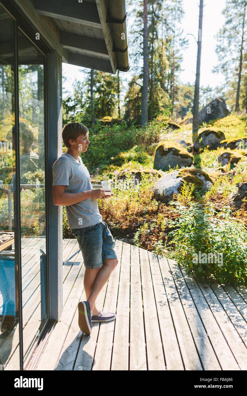 Finlandia, Uusimaa, Sipoo, vista laterale del giovane con tazza di caffè sul portico Immagini Stock